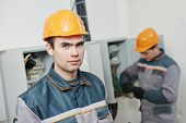 image of fuse-box  - two electrician builder engineer workers in front of fuse switch box - JPG