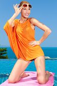 picture of infinity pool  - Sexy gorgeous woman posing poolside kneeling on a towel in a short orange top lifting her sunglasses with a happy smile as she looks to the side  infinity pool overlooking the ocean - JPG