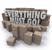 picture of going out business sale  - Everything Must Go words in 3d letters surrounded by cardboard boxes in a store warehouse to illustrate overstock inventory for a sale or clearnace event - JPG