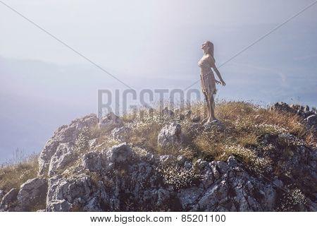 Young girl on top of mountain enjoying life