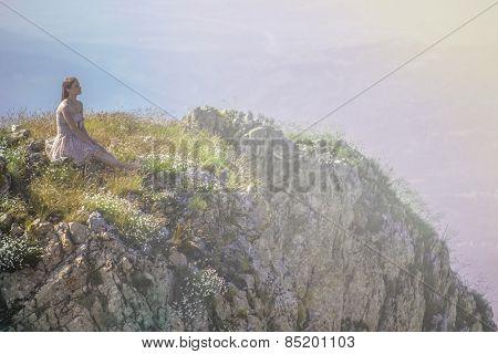 Young girl sitting on top of mountain enjoying life