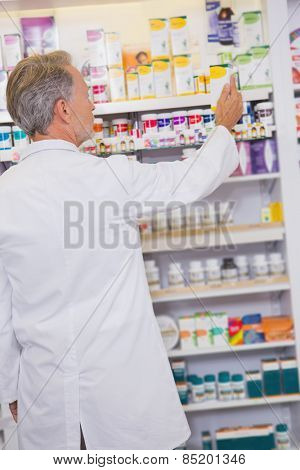 Senior pharmacist taking box from shelf in the pharmacy