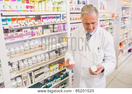 Smiling pharmacist looking at medications in the pharmacy