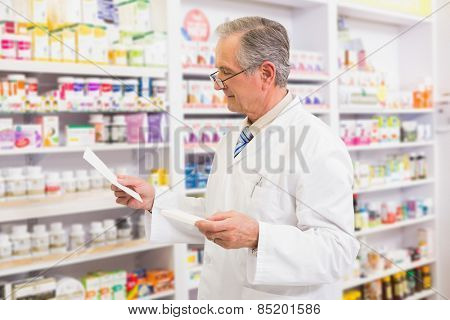 Senior pharmacist looking at medicine and prescription in the pharmacy