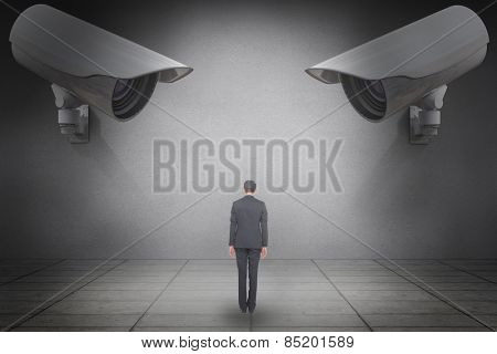 Businessman turning his back to camera against grey room