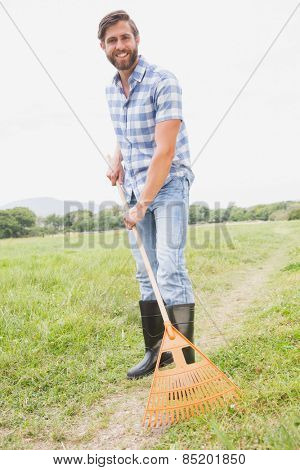 Happy man raking his farm on a sunny day