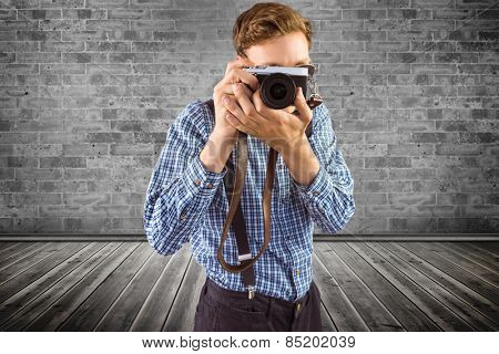 Geeky hipster holding a retro camera against grey room