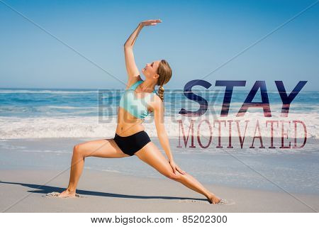 Fit woman standing on the beach in warrior pose against stay motivated