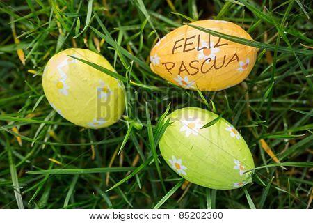 feliz pasqua against three easter eggs wrapped in foil