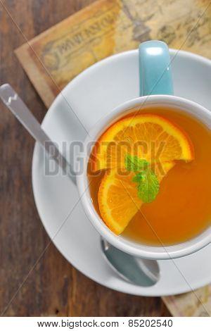 Tea and orange slices on old wood table