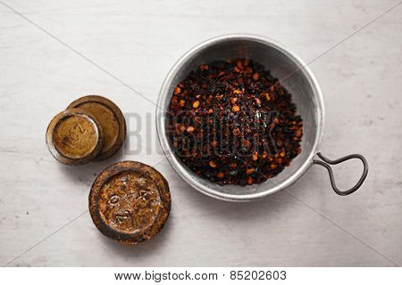 chipotle - jalapeno smoked whole chili  in tin bowl on  textured  metal backdrop