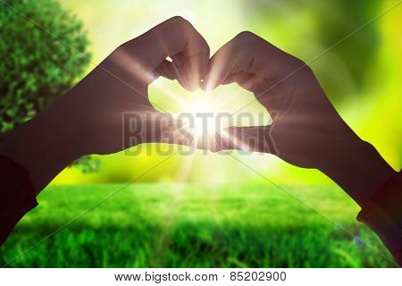Woman making heart shape with hands against field against glowing lights