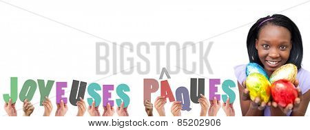 Hands holding up joyeuses pasques against attractive woman holding colorful easter eggs