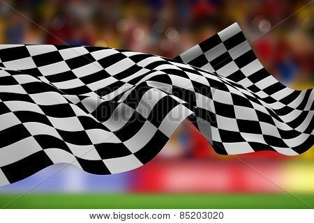 Checkered flag against blurry football pitch with crowd