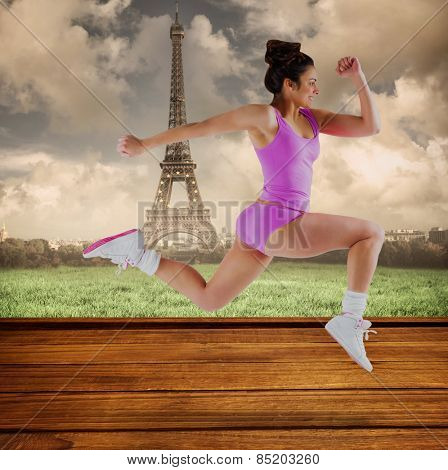 Fit brunette running and jumping against wooden planks against eiffel tower