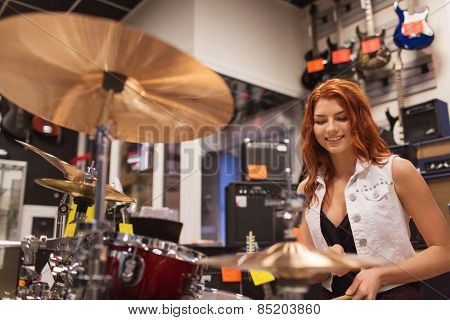 music, sale, people, musical instruments and entertainment concept - smiling female musician playing cymbals at music store