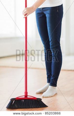 people, housework, cleaning and housekeeping concept - close up of woman legs with broom sweeping floor at home