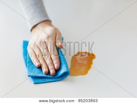 people, housework and housekeeping concept - close up of woman hand cleaning dirty table surface with cloth at home
