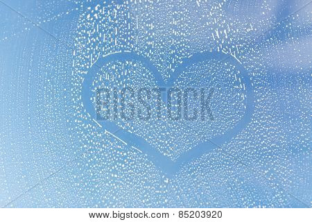 people, housework, love, valentines day and housekeeping concept - close up of heart shape drawing on soapy window glass