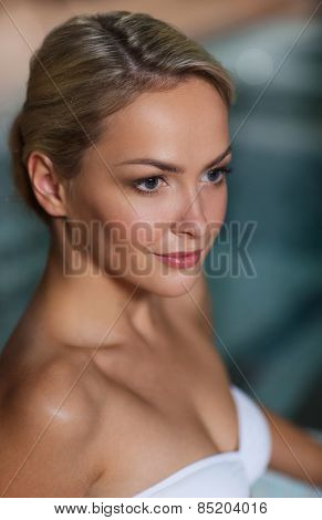 people, beauty, spa, healthy lifestyle and relaxation concept - close up of beautiful young woman in swimsuit at swimming pool