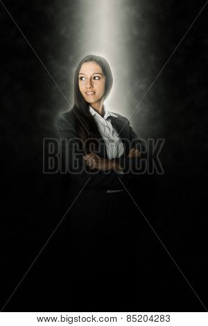 Glowing Head of a Young Female Business Executive Crossing her Arms Over her Body While Looking Far Left of the Frame on an Abstract Black Background