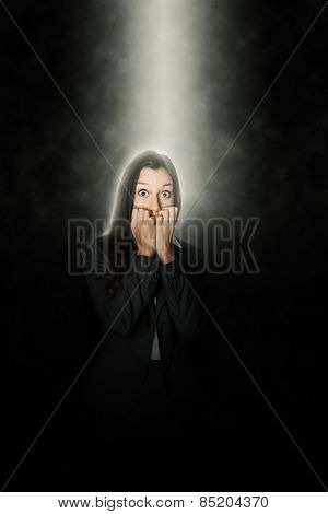 Terrified woman standing in a beam of white light shining down through the darkness from above looking at the camera with terror in her eyes and biting her nails in suspense