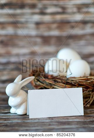 Close up Bunny Porcelain and Chicken Eggs in Nest with Blank Note Paper on Top of Wooden Table, Emphasizing Copy Space.