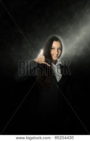 Happy Asian businesswoman giving a call me sign or gesture with her fingers in a communication concept as she stands in a beam of light