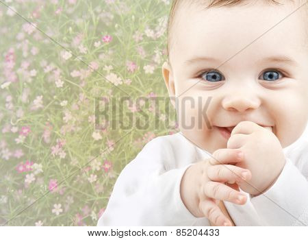people, childhood, spring and happiness concept - close up of happy smiling baby over floral background