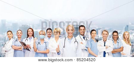 medicine and healthcare concept - team or group of doctors and nurses showing thumbs up