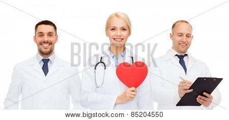 medicine, profession, teamwork and healthcare concept - group of smiling medics or doctors holding red paper heart shape, clipboard and stethoscopes over white background