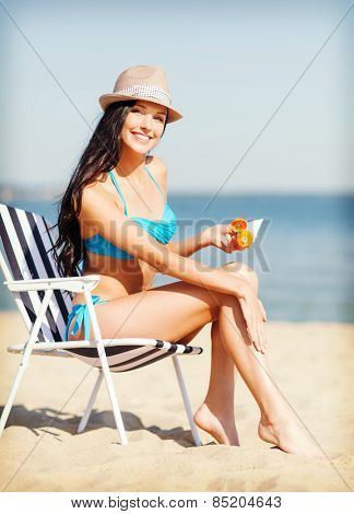 summer holidays and vacation - girl putting sun protection cream on the beach chair