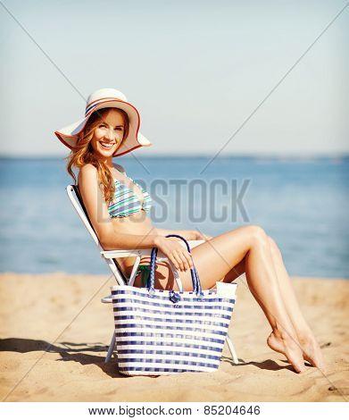 summer holidays and vacation - girl in bikini sunbathing on the beach chair