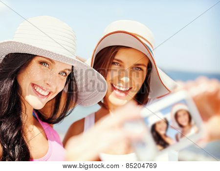 summer holidays and vacation concept - girls taking self portrait on the beach