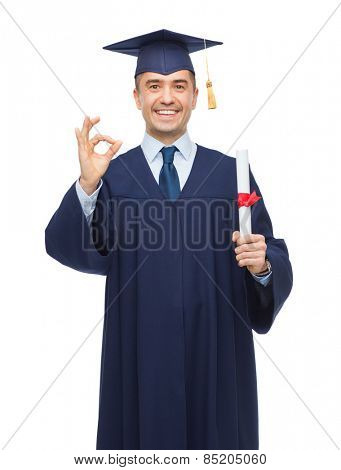 education, graduation, gesture and people concept - smiling adult student in mortarboard with diploma showing ok hand sign