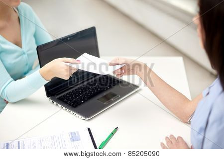 medicine, health care, meeting and people concept - close up of female doctor with laptop computer giving prescription to patient at hospital