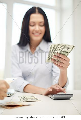 finances, currency, exchange rate, technology and people concept - close up of happy woman counting dollar money with calculator