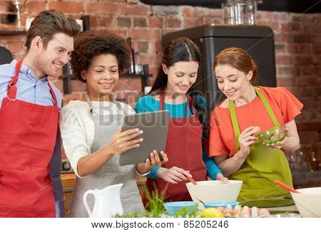 cooking class, friendship, food, technology and people concept - happy friends with tablet pc computer in kitchen