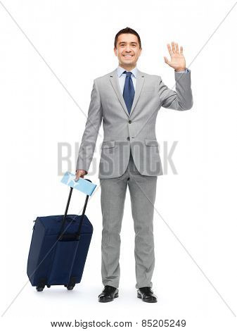 business trip, traveling, luggage and people concept - happy businessman in suit with travel bag and air ticket waving hand