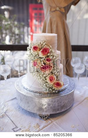 Beautiful three tiered wedding cake with roses, shallow focus on roses