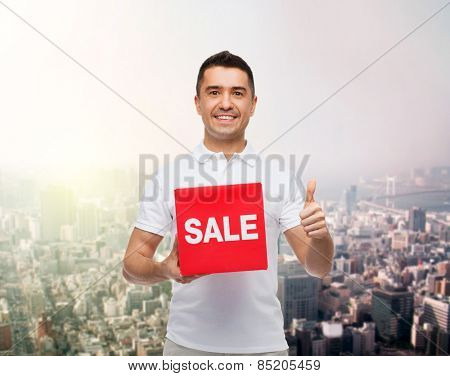 shopping, discount, consumerism, gesture and people concept - smiling man with red sale sigh showing thumbs up over city background