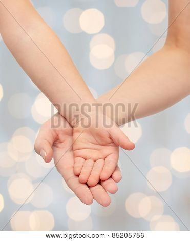 people, charity, family, children and advertisement concept - close up of woman and little child hands holding empty palms over holiday lights background