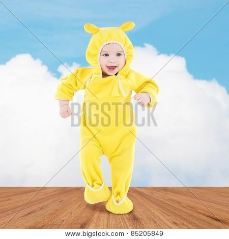 people, children, achievement and happiness concept - happy baby in yellow suit making first steps over wooden floor and blue sky background