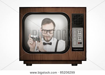 Geeky hipster holding a retro camera against retro tv