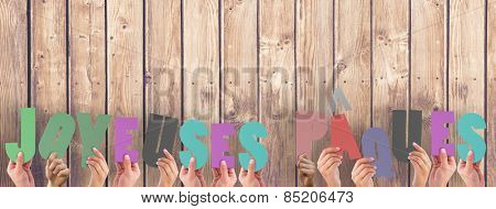 Hands holding up joyeuses pasques against wooden planks