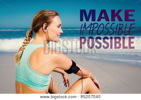 Fit woman sitting on the beach taking a break smiling against make impossible possible