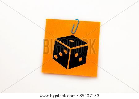 Dice against orange adhesive note with a paperclip