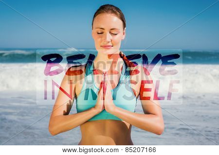 Fit woman meditating on the beach against believe in myself