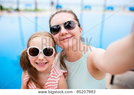 Happy mother and her adorable little daughter outdoors near a swimming pool taking selfie at tropical resort