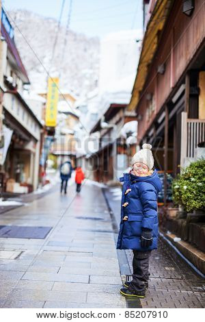 Little girl at old district of hot spring resort town Shibu onsen in Japan on winter day